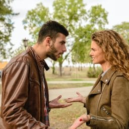 man and woman facing each other arguing in a park