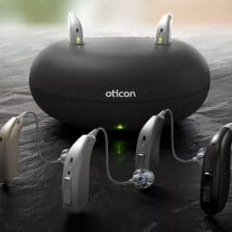 Oticon hearing aids in front of a charging base