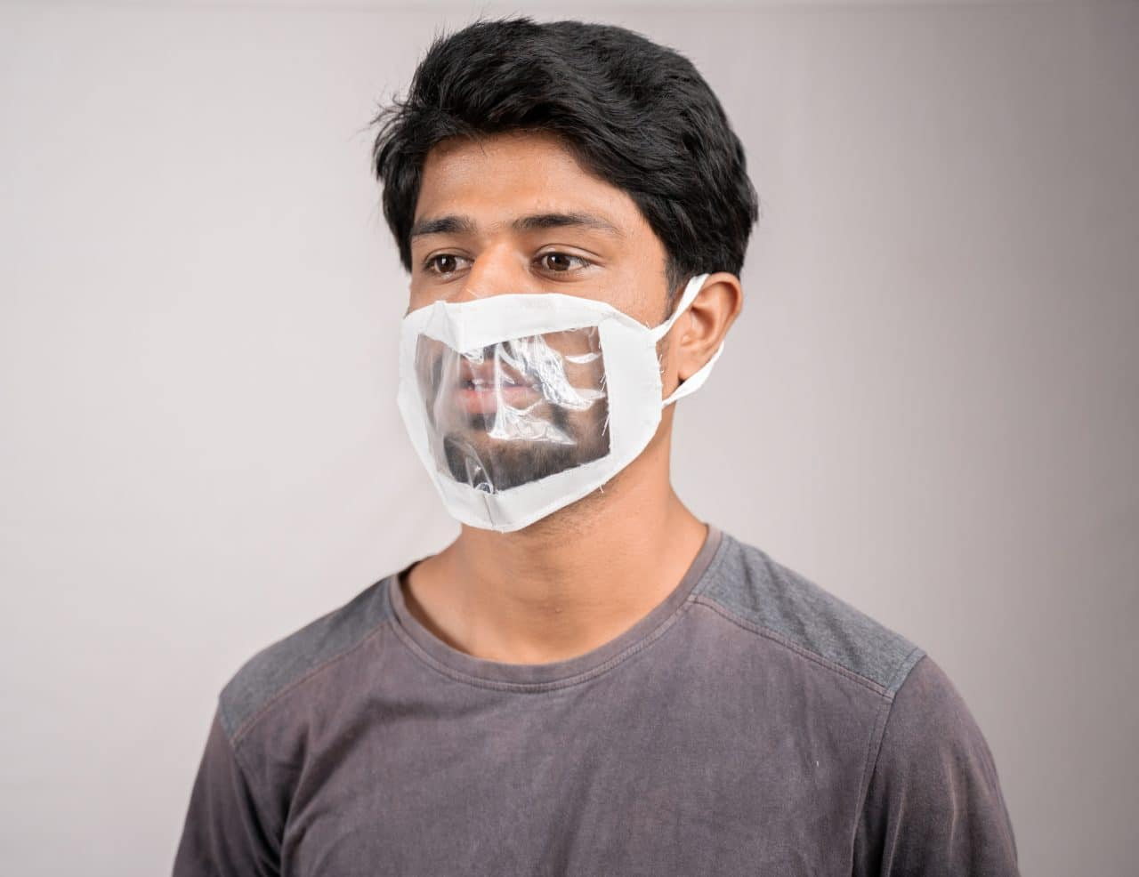 young man with transparent Medical face mask, to help hearing impermeant or deaf people to understand lipreading during coronavirus or covid-19 outbreak