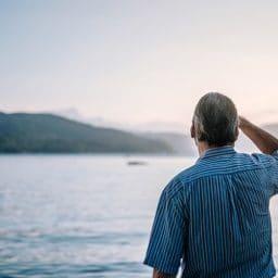 Man looking out at lake.