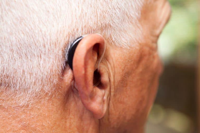 Senior man wearing a discrete, modern hearing aid.