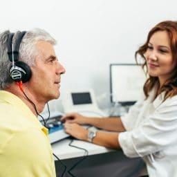 An older man receives a hearing test.